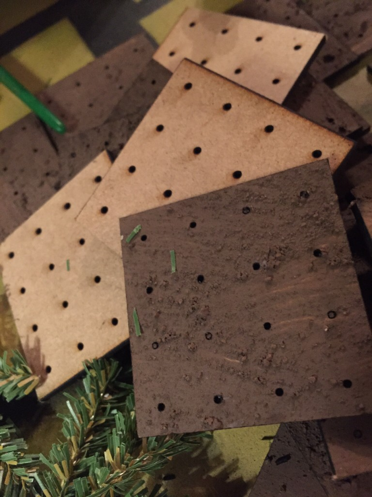 Laser cut 2 inch square bases with 16 holes each.